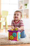 Baby toddler playing with sorter toy sitting on soft carpet at home. Baby toddler boy plays at home with sorter toy sitting on soft carpet Royalty Free Stock Image