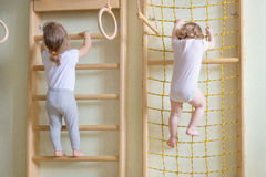 Baby toddlers climbing up the stairs. Two baby toddlers climbing up the gymnastic stairs Royalty Free Stock Images