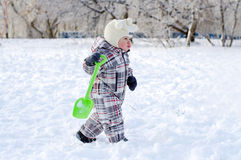 Baby toddles with shovel in winter Royalty Free Stock Images
