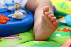 Baby toes. Close up of babies foot surrounded by toys Stock Photography