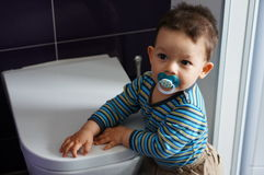 Baby by toilet Stock Photo
