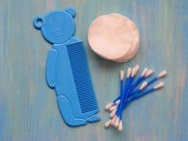 Baby-Toilettenartikel-Einzelteile, Werkzeuge benutzt für Babys auf blauem hölzernem Hintergrund lizenzfreies stockfoto