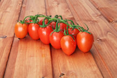 Baby tomatoes on a stem placed on wooden pad Royalty Free Stock Photo