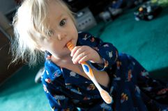 Baby With Toothbrush. A baby in pajamas try's to figure out this toothbrush thing Royalty Free Stock Photo
