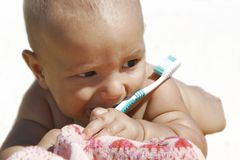 Baby with toothbrush Stock Images
