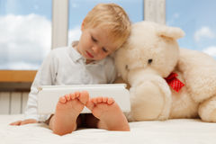 Baby with touch pad. Baby and teddy bear with touch pad at home Stock Photography