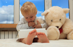 Baby with touch pad. Baby and teddy bear with touch pad at home Royalty Free Stock Image