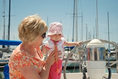 Baby touches wheel on a sailboat Royalty Free Stock Images