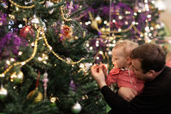 Baby touching bulb on Christmas tree Stock Image
