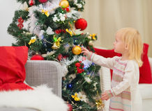 Baby touching Christmas ball on Christmas tree Royalty Free Stock Photos