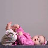 Baby touching his leg Royalty Free Stock Photos