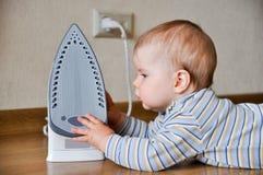 Baby touching hot iron Stock Photo