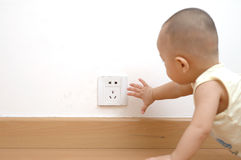 Baby touching power socket. A chinese baby wants to touching the AC power socket Stock Photography