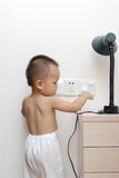 Baby touching power socket. A chinese baby wants to touching the AC power socket and the table lamp Royalty Free Stock Photos