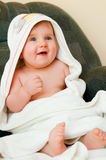 Baby in towel. Smiling baby girl sits wrapped in a towel after bath Royalty Free Stock Photography