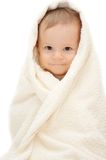 Baby in towel. Sitting on the floor stock image
