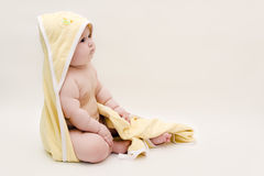 A baby in a towel. Beautiful baby after a bath sits on the floor in towel royalty free stock photo