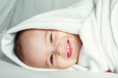 Baby with a towel. Happy one year old baby wearing diapers with a towel in bed at home Royalty Free Stock Image