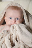 Baby with a towel after the shower in bed at home Stock Photo
