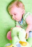 Baby with toy. Portrait of a cute baby with green soft toy Stock Photo