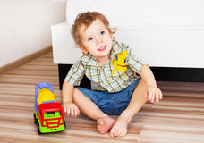 Baby with a toy. Car on the floor at home Stock Photos