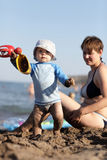 Baby with toy on beach Royalty Free Stock Photo