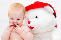 Baby with a toy bear. A little girl with a toy teddy bear and a pacifier in her hand stock photo