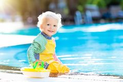 Baby in swimming pool. Family summer vacation. Baby with toy boat in swimming pool. Little boy learning to swim in outdoor pool of tropical resort. Swimming Stock Image