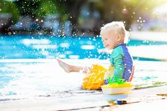 Baby in swimming pool. Family summer vacation. Baby with toy boat in swimming pool. Little boy learning to swim in outdoor pool of tropical resort. Swimming stock photos