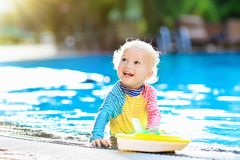 Baby in swimming pool. Family summer vacation. Baby with toy boat in swimming pool. Little boy learning to swim in outdoor pool of tropical resort. Swimming Royalty Free Stock Image