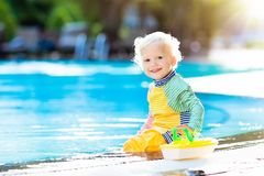 Baby in swimming pool. Family summer vacation. Baby with toy boat in swimming pool. Little boy learning to swim in outdoor pool of tropical resort. Swimming Stock Photo