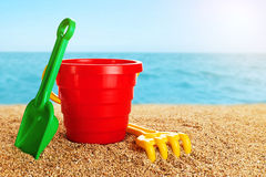 Baby toy bucket, shovel and rake in the sand. Stock Image