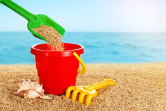 Baby toy bucket, shovel and rake in the sand. Stock Photography