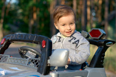 Baby in a toy car Stock Images