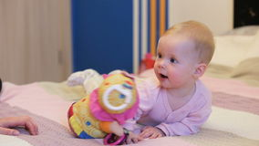 Baby with a toy. Cute baby with toy lying on the bed.Little bay looking at toy in his mother's hand stock footage