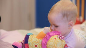 Baby with a toy. Cute baby with toy lying on the bed.Little bay looking at toy in his mother's hand stock video