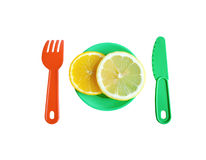 Baby toy Cutlery and fruit. Cut the slices of orange and lemon in a small childs plate. Next a plastic knife and fork Royalty Free Stock Photography