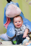 Baby and toy donkey. Baby sitting with his fovourite toy donkey Stock Photos