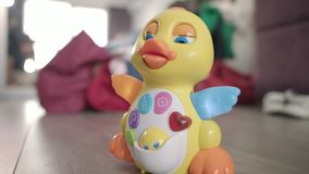 Baby toy duck moving on floor. Musical toy with button and lights moving. Baby toy duck moving on floor. Child entertain. Learning toys in baby room. Musical toy stock footage