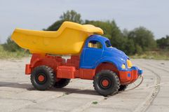 Baby toy dump truck on sunny road Stock Photos