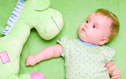 Baby with toy giraffe. Portrait of a cute baby with green soft toy Stock Photos