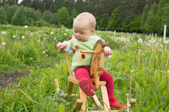 Baby on a toy horse on farm Royalty Free Stock Photos