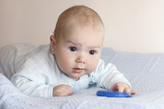 The baby with a toy. The little boy lies on a stomach with a toy Royalty Free Stock Photo