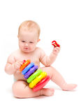 Baby with a toy and pacifier. Naked cute baby with colorful toy and pacifier in hand on white background stock photo
