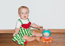 Baby with toy sits. Little baby boy in watermelon suit sits near plastic toy Stock Photography