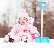 Baby with a toy spade. Happy one year old baby girl with a toy spade outdoor on a winter day stock images