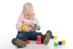 Baby with toys. The little girl sitting on the floor and playing with toys Stock Photography