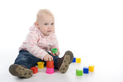 Baby with toys. The little girl sitting on the floor and playing with toys Stock Photos
