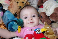 Baby with toys. Image of a baby girl surrounded by toys Stock Photos