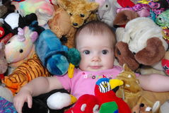 Baby with toys. Image of a baby girl surrounded by toys Royalty Free Stock Image
